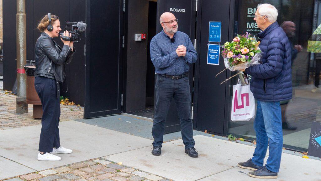 TV2 Østjylland var på pletten, da BMA overraskede gæst nr. 100.000. På billedet: Museumschef Jørgen Smidt-Jensen (i midten) og Ejvind Skytte Christensen, som modtog blomster, champagne og en boggave.